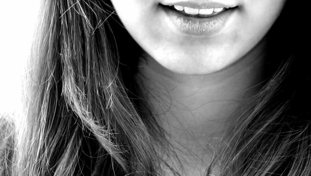 woman smiling in grayscale photography